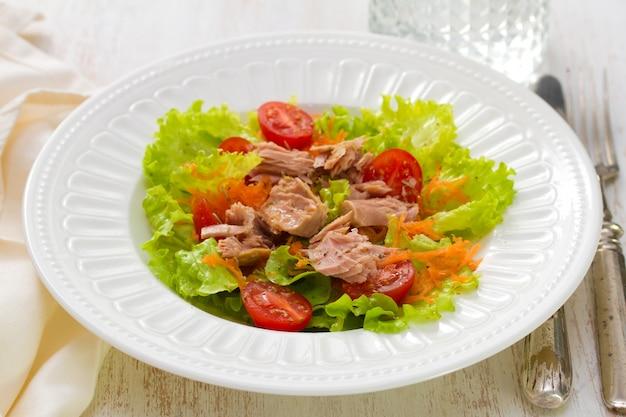 Салат из тунца на белой тарелке на белом