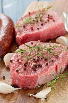 スモークソーセージ、コショウ、木の板にニンニクと生肉