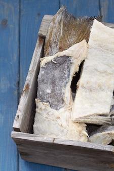 青い木製の背景に木製の箱で塩漬けのタラ魚