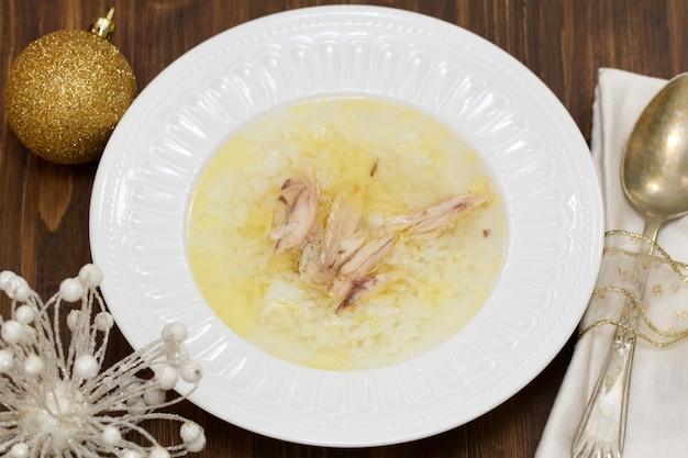 ご飯と鶏肉の白い皿に鶏肉入りスープ