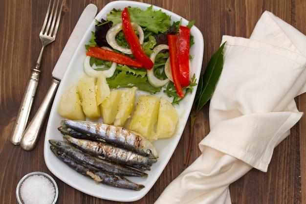 茶色の木製の白い皿にポテトとサラダと揚げイワシ