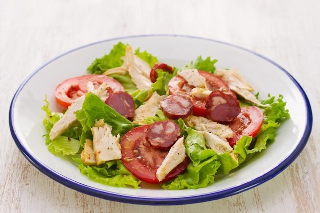 鶏肉と白い木製のテーブルに白い皿にチョリコのサラダ