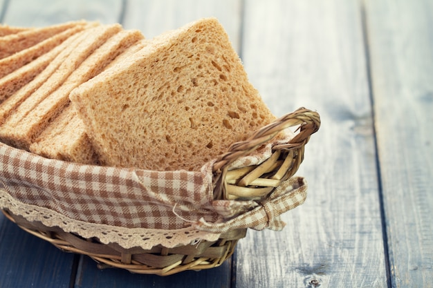 Хлеб в корзине на синем деревянном столе