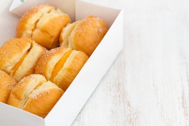 木製の表面にホワイトペーパーボックスに卵クリームとドーナツ