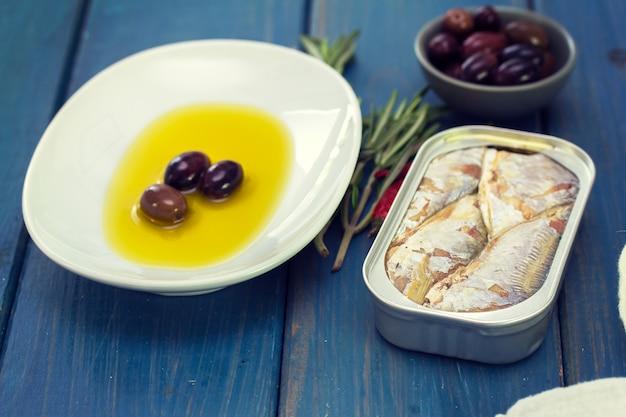 Рыба в железе с черными оливками на синей поверхности