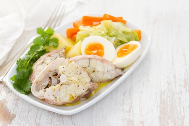 白い皿に野菜をゆでた魚