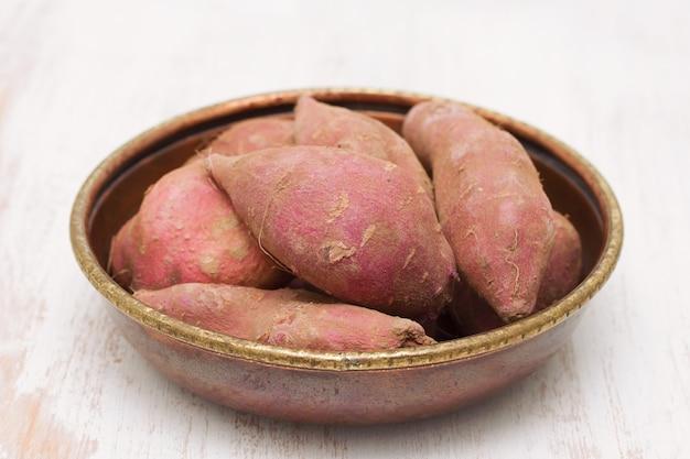 木製の背景に皿にサツマイモ