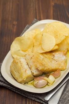 ニンニクとポテトの皿に揚げたタラ