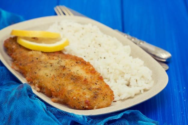魚のフライ、レモンとご飯を皿に