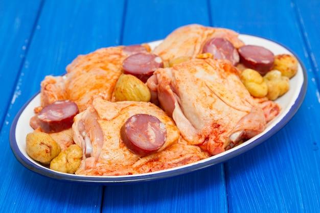 Сырая маринованная курица с копчеными колбасками на блюде