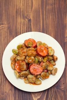 白い皿にスモークソーセージと豆