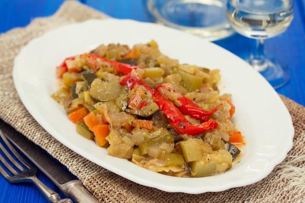 木の表面に白い皿に野菜のシチュー