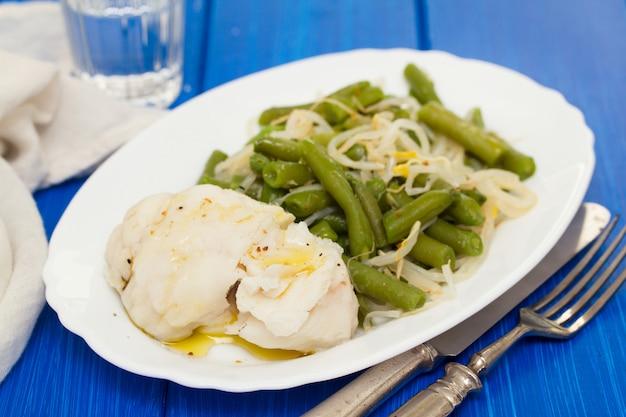 Вареная рыба с зеленой фасолью на белом блюде
