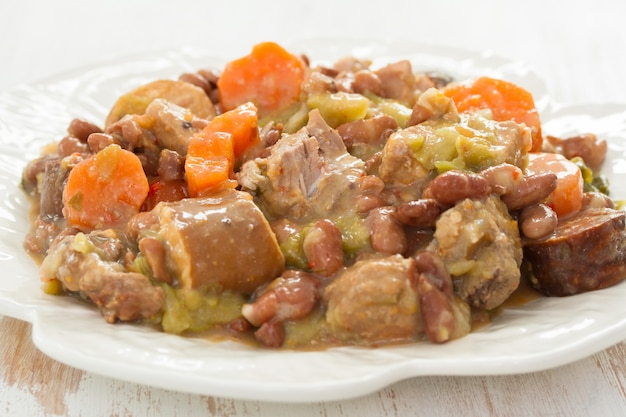 Мясо с овощами и колбасками на тарелке
