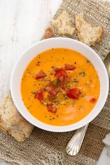 木製の表面に白いボウルにトマトのスープ