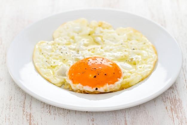 Жареное яйцо на белой тарелке на деревянной поверхности