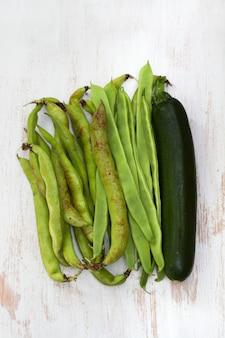 白い木製の表面に緑の新鮮な野菜