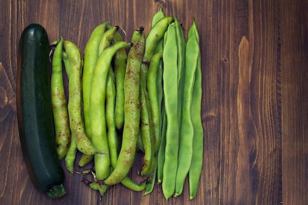 茶色の木製の表面に緑の新鮮な野菜