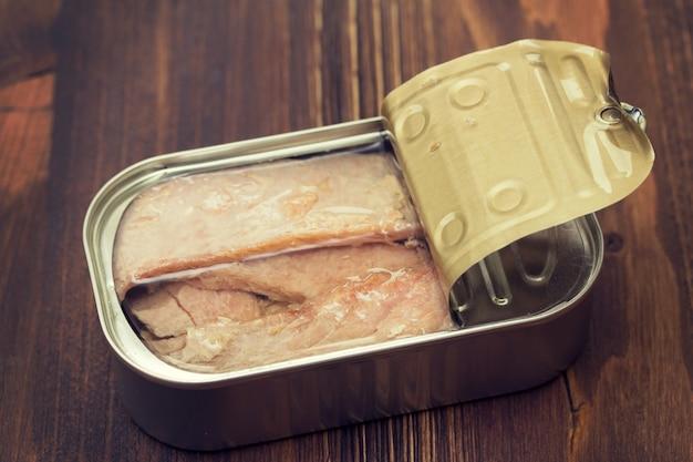 Рыба в масле на железной коробке на деревянной поверхности