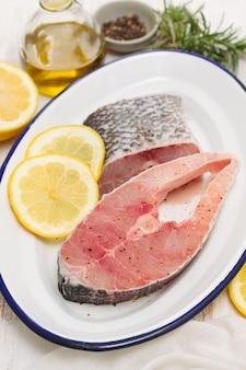 木製の表面に皿にレモンと生の魚