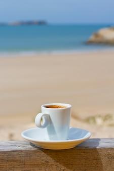 ビーチの景色とコーヒーのカップ