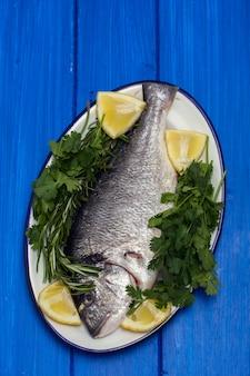 ハーブとレモンの木の表面に皿に生の魚
