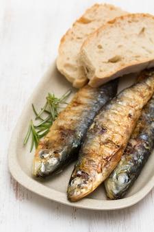 Жареные сардины с хлебом на блюде