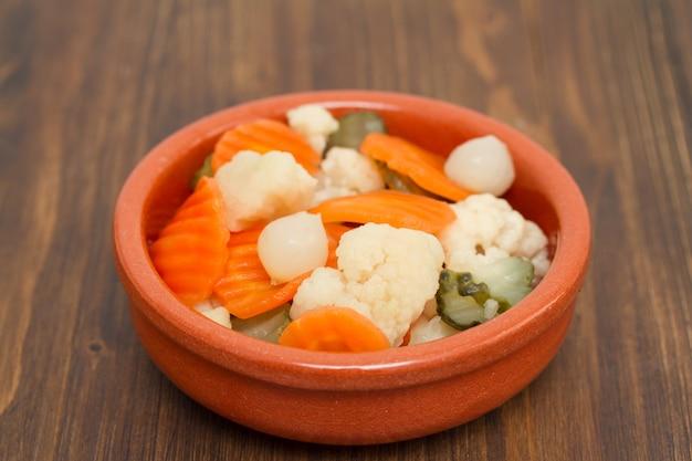 Маринованные овощи в керамическом блюде на деревянной поверхности