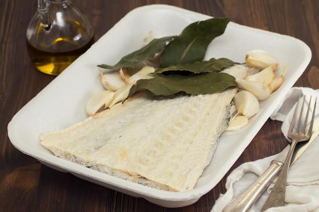 Рыба соленая треска с лавровым листом на блюде