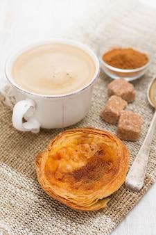 一杯のコーヒーと伝統的な卵のタルトパステルデナータ