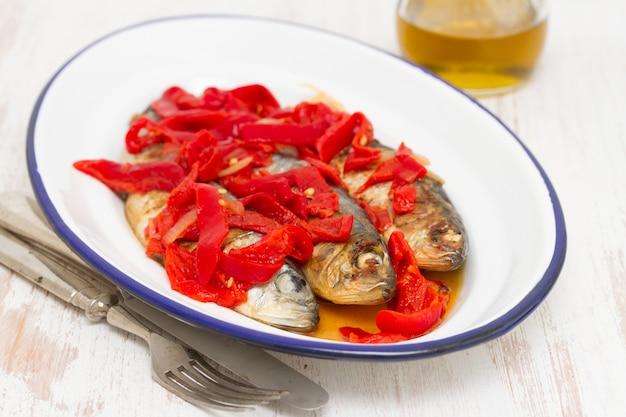 Жареные сардины с красным перцем на белом блюде