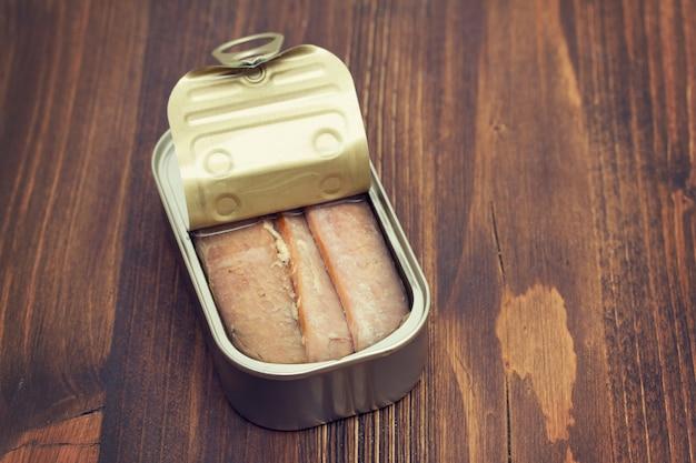 Тунец в железной коробке на деревянной поверхности
