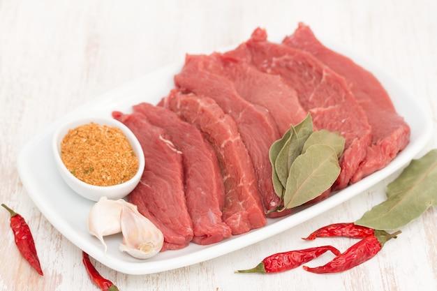 木の表面に白い皿にハーブと生の肉