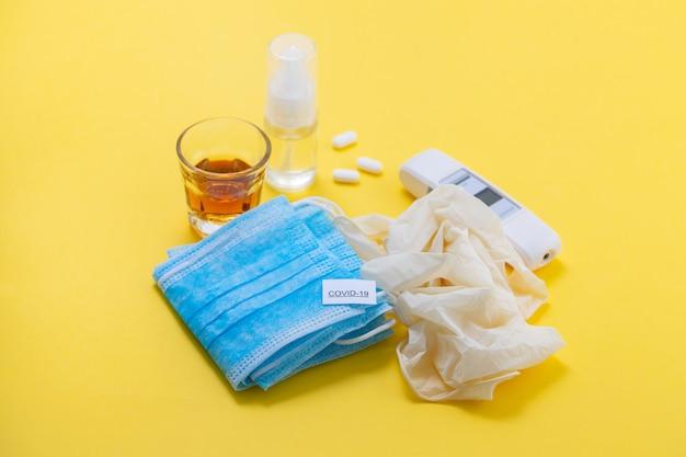 Медицинская маска, перчатки и дезинфицирующее средство на желтом фоне