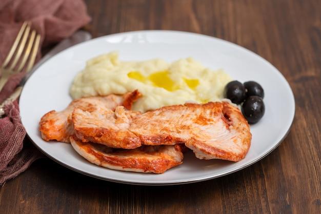 Жареная индейка с картофельным пюре и оливками на белом блюде