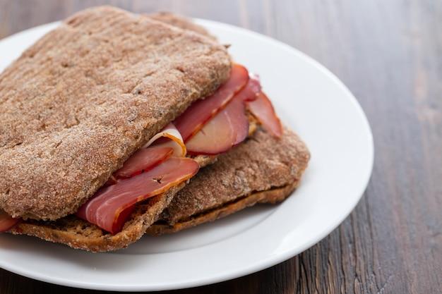Темный хлеб с копченым мясом на белой тарелке