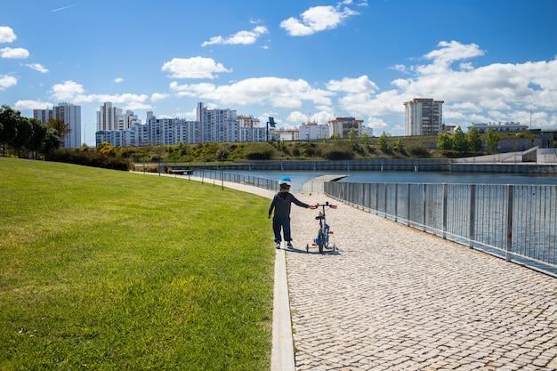 Мальчик с велосипедом в городском парке