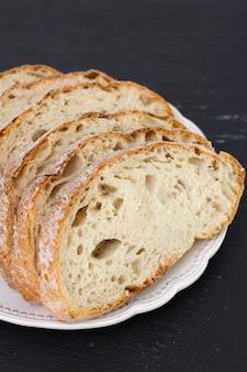 Хлеб на тарелке на черном фоне