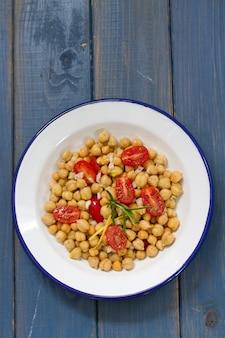 Салат из нута и помидоров на белой тарелке на синей поверхности