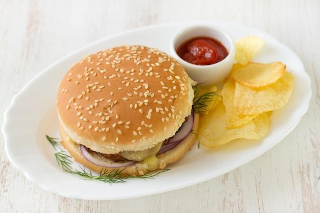 チップスと皿にソースのハンバーガー