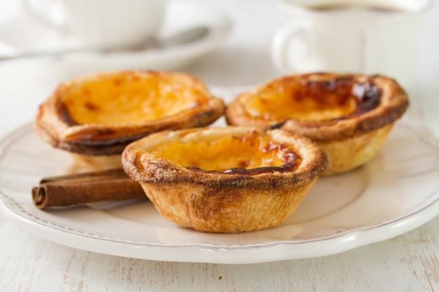 Португальское печенье с корицей на белом блюде с чашкой кофе