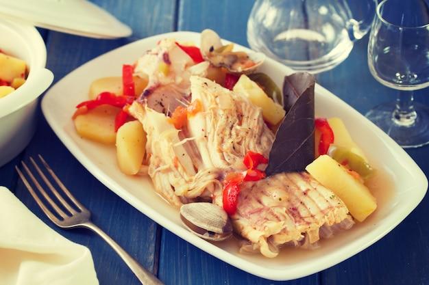 青い木製の表面にワインと白い皿に魚のシチュー