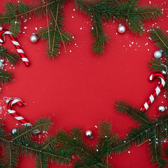 Красная квартира лежала минималистичный рождественский квадратный баннер с еловые ветки и конфеты, елки и игрушки.