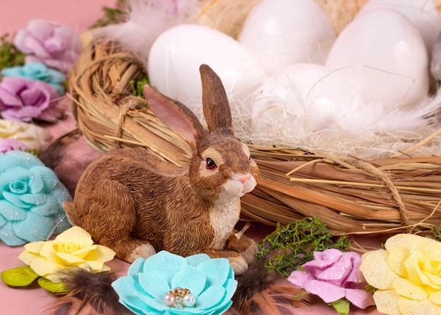 Весеннее настроение, пасхальный декор из яиц, бумажные цветы, венок из лозы и маленькие милые кролики на фоне живого коралла. широкий баннер - изображение.
