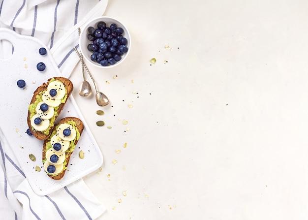 アボカドとブルーベリーのサンドイッチ。幸せな朝の朝食白い背景の上の健康食品のコンセプト。スペースをコピーします。上面図。