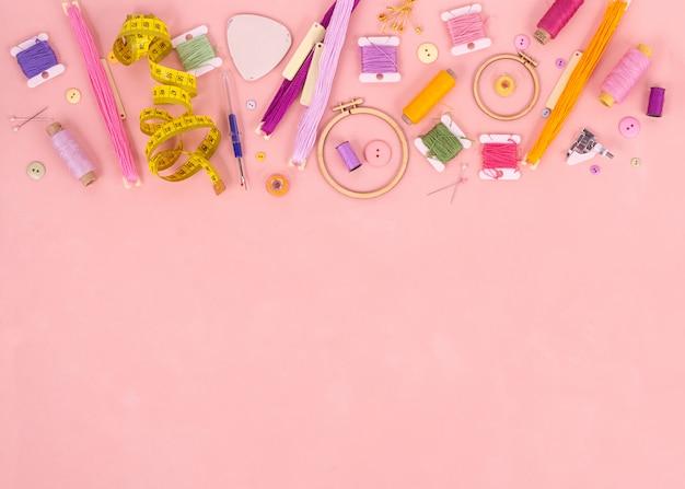 ピンクの背景に刺繍とクロスステッチのアクセサリー。平らに置きます。スペースをコピーします。