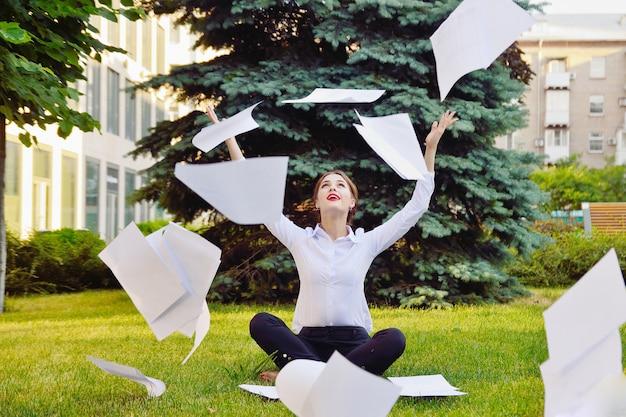 オフィスヨガ。ロータスポーズのビジネス女性は緑の草の上に座って頭の上に紙を投げます。