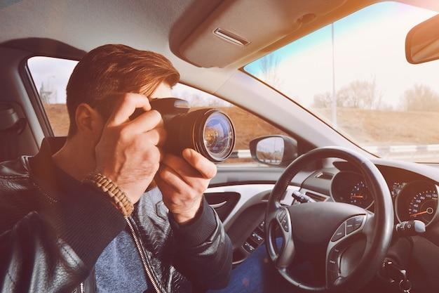 男が車の窓から写真を撮っています。