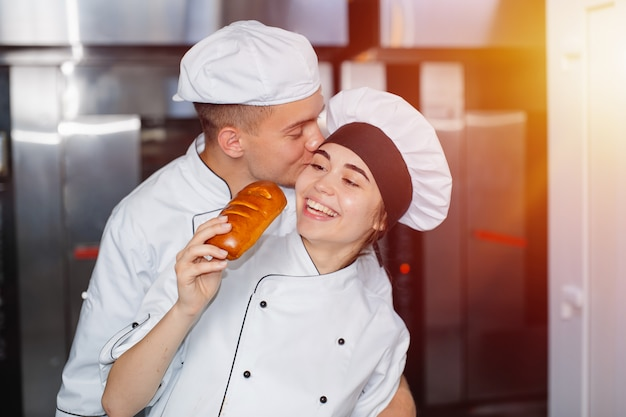Мальчик-пекарь целует девушку в щеку в пекарне на фоне духовки.
