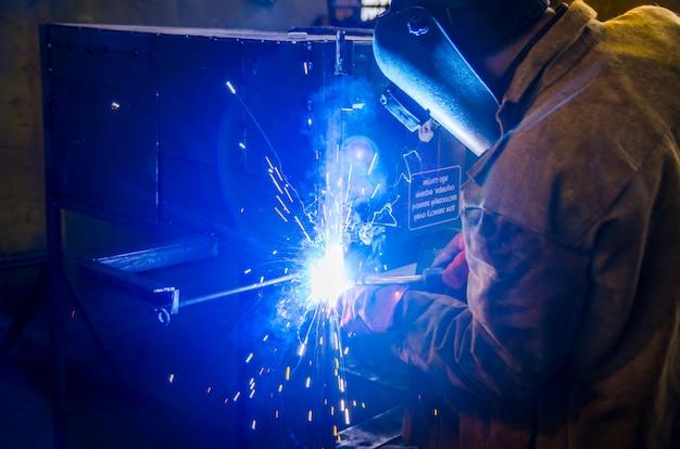 Рабочий в спецодежде и защитной маске сваривает металл сварочным аппаратом